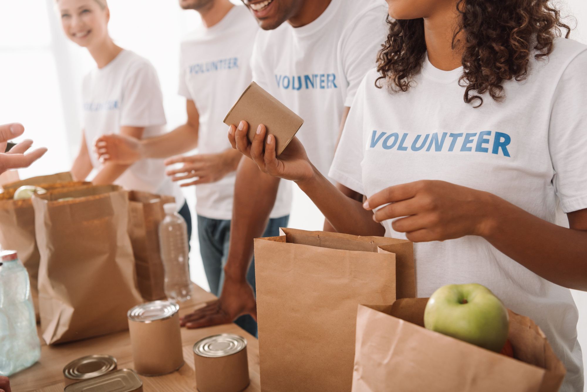 Cropped shot of young volunteers group packing food and drinks for charity