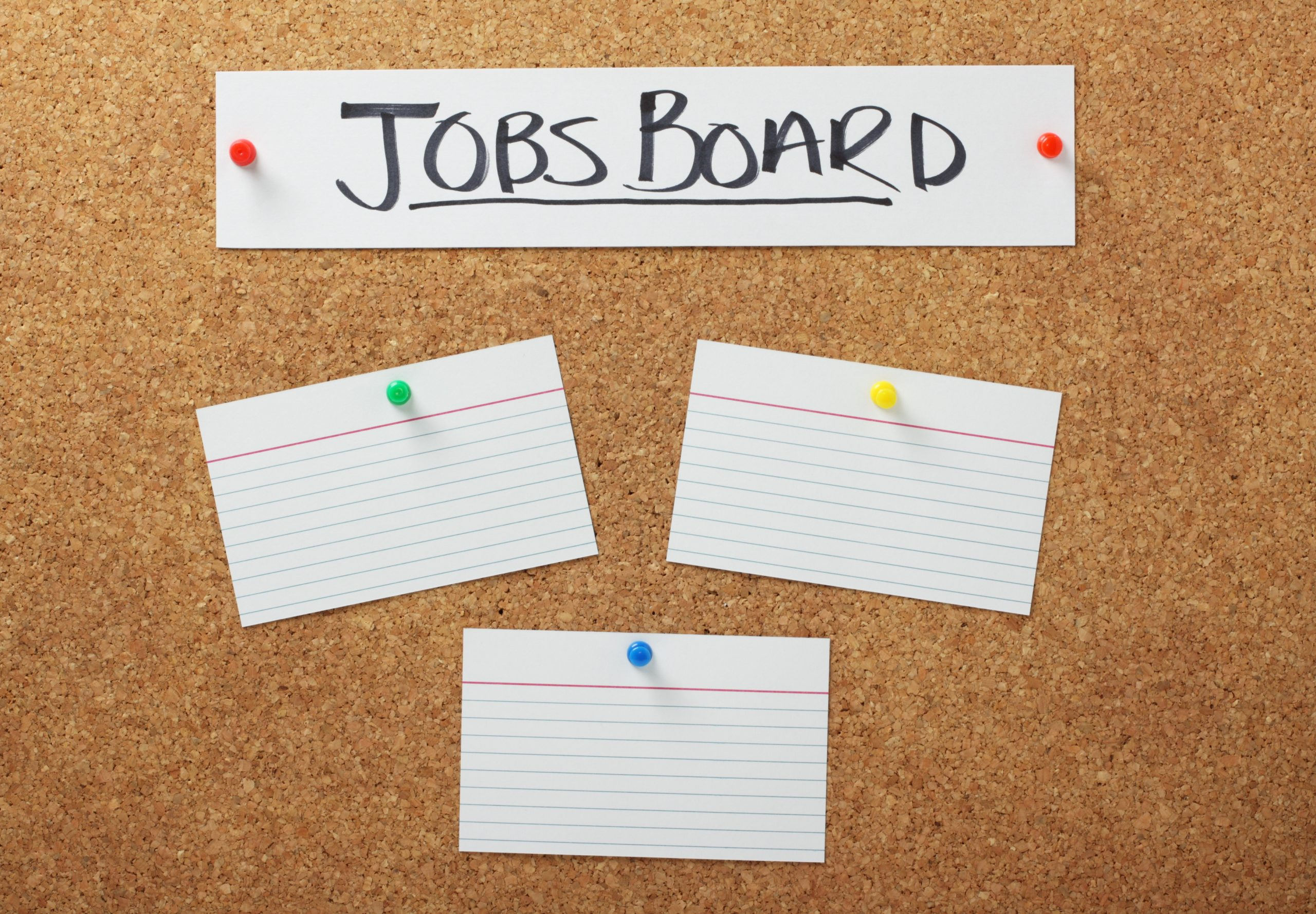A Jobs Board banner on a cork notice board with blank white note cards for copy space